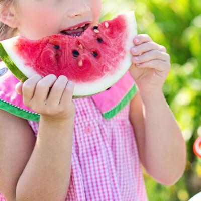 a girl eats a watermelon