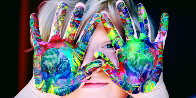 A child shows their colorful painted hands