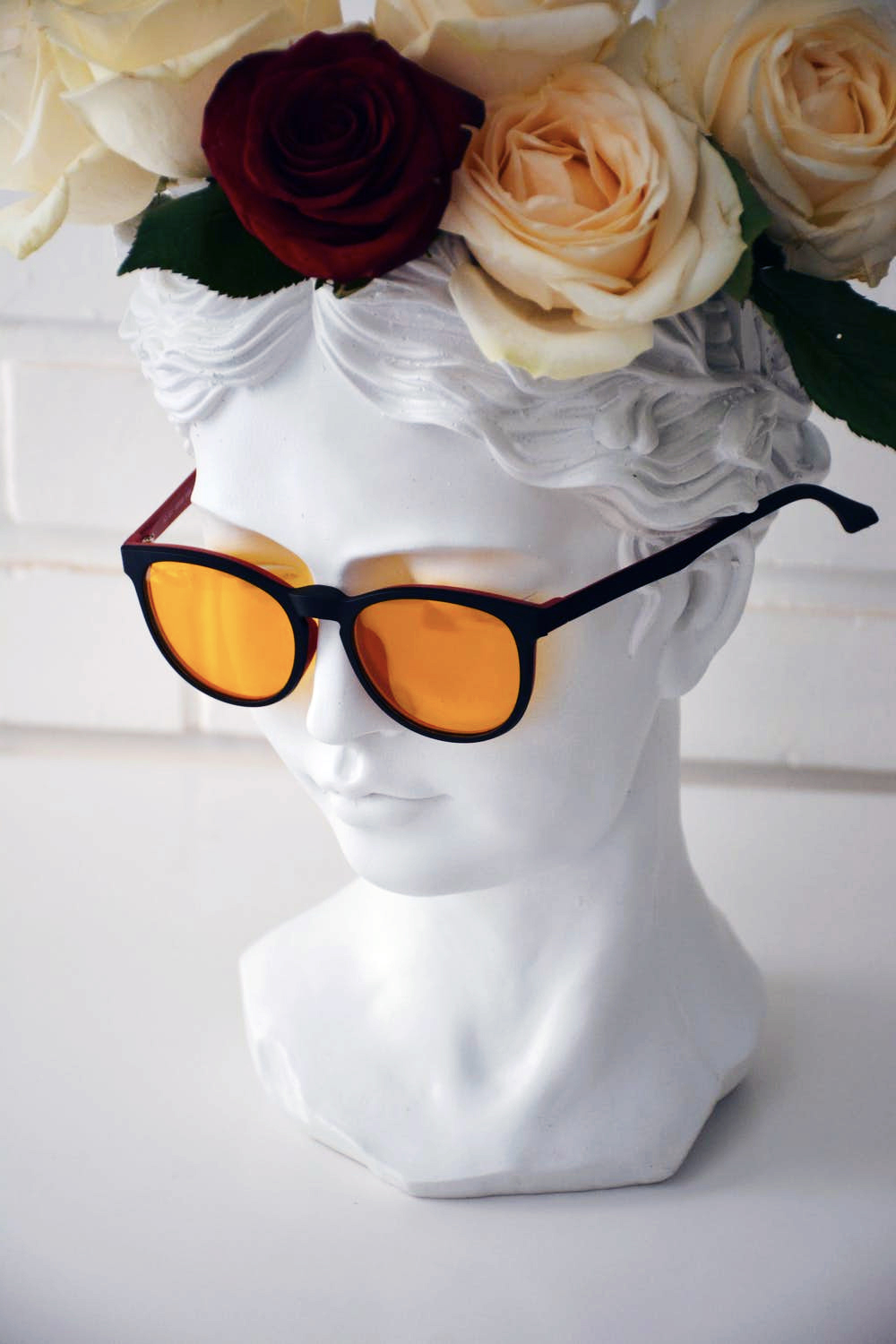 A portrait bust in a flower wreath and sunglasses